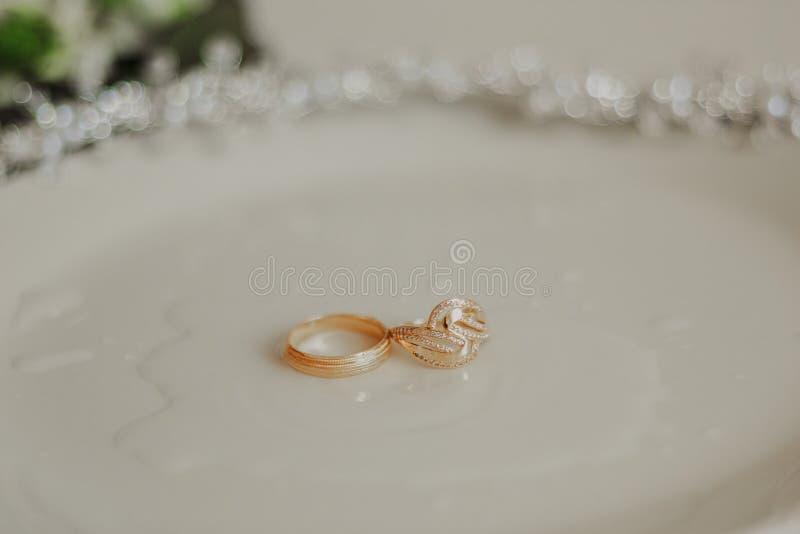 挺直两金结婚戒指横幅,象征爱和浪漫史,在织地不很细白色衣服饰物之小金属片背景与拷贝 免版税库存照片