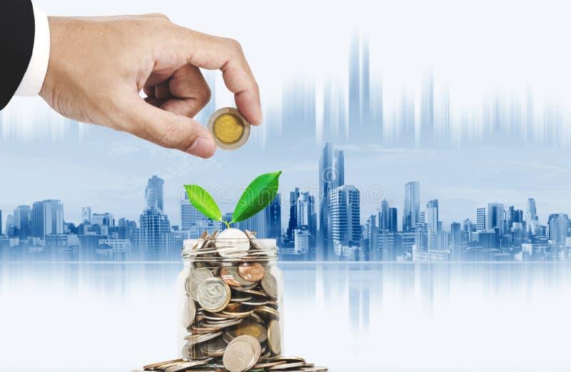 挽救金钱和投资概念 递投入硬币在有生长的植物的,曼谷市背景玻璃瓶子 免版税库存图片