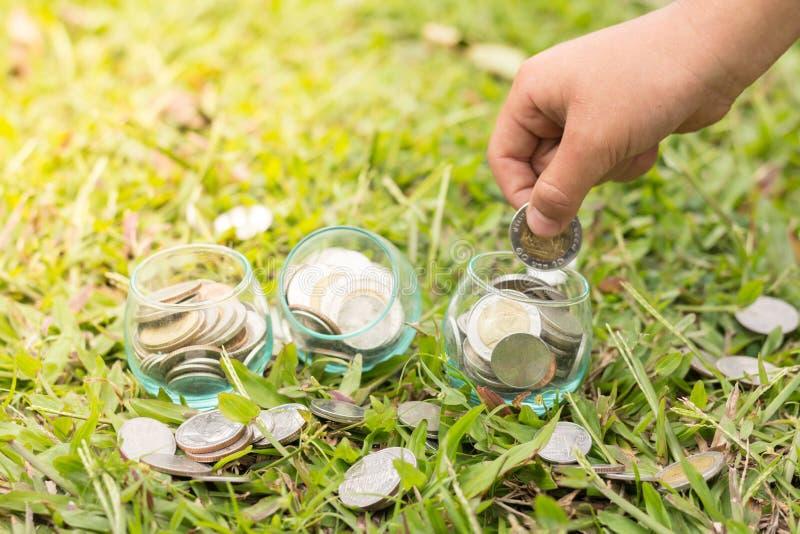 挽救金钱概念,投入金钱硬币堆生长事务的男性手 免版税库存图片