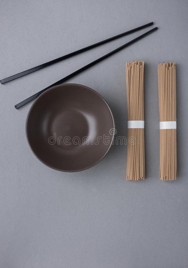 捆绑在灰色背景的Soba面条黑暗的空的碗紫竹筷子 日本中国亚洲烹调 菜单海报 免版税图库摄影