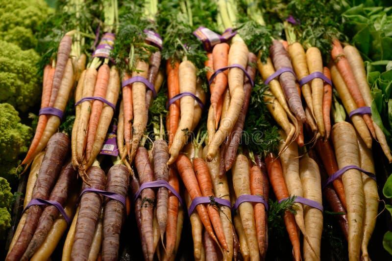 捆绑彩虹红萝卜在市场上 库存照片
