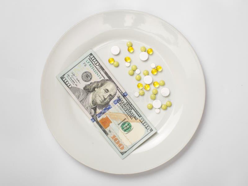 捆绑在一块白色板材的金钱有药片的 免版税库存图片