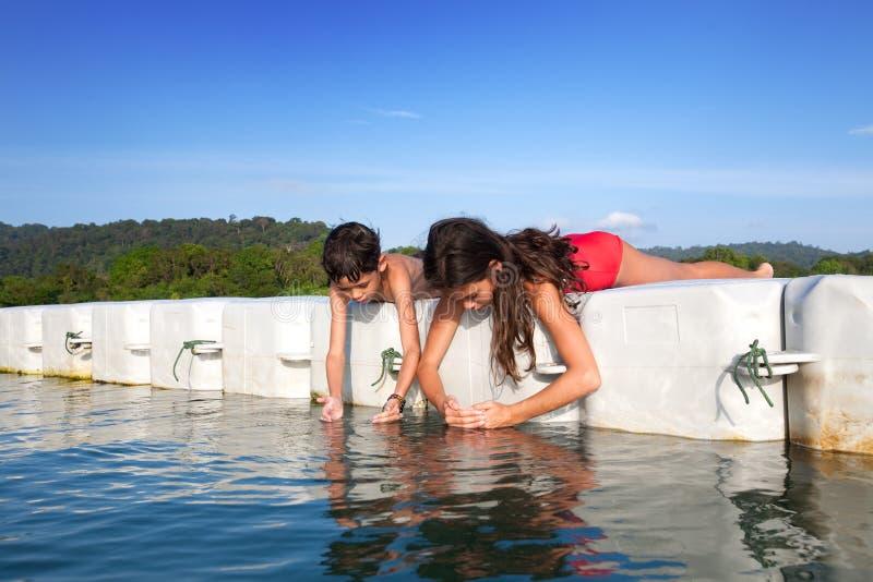 捉住微小的大虾的男孩和他的姐妹,当他们在热带海岛上时的浮动平台 免版税库存图片