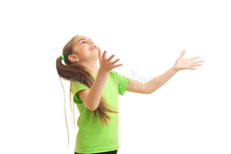 捉住某事的绿色衬衣的滑稽的小女孩 免版税库存图片