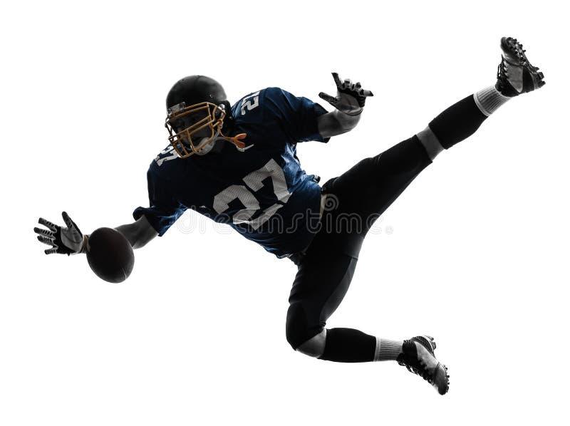 捉住美国橄榄球运动员的人接受剪影 库存照片