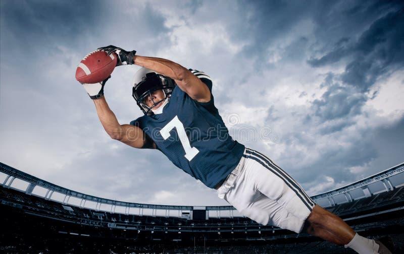 捉住触地传球的美国橄榄球运动员 免版税库存照片