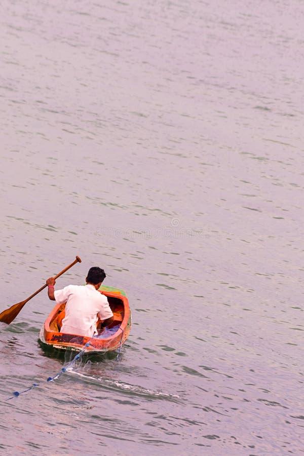 捉住鱼净出口的独木舟小船的基本的渔夫对公海浸洗设陷井透视图 免版税图库摄影