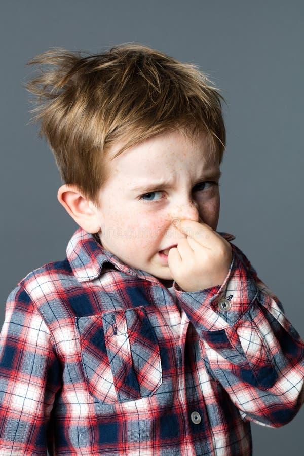 捏他的鼻子的害怕的小孩由坏气味懊恼了 免版税库存照片