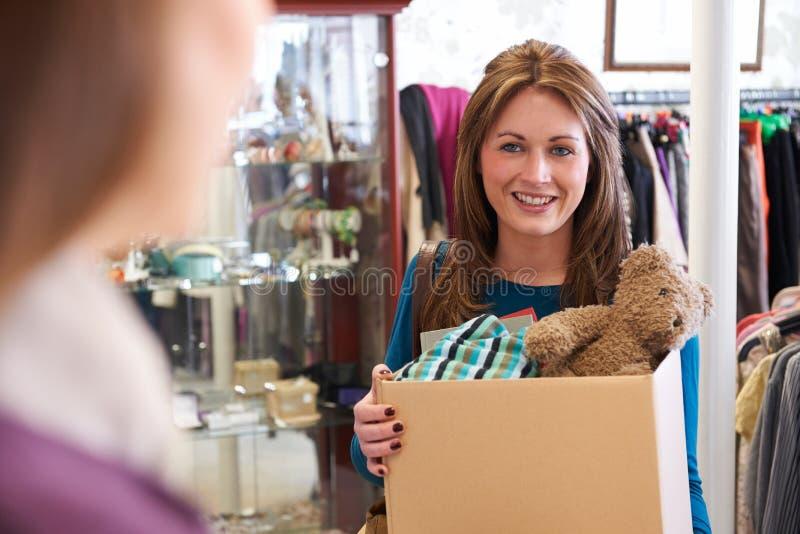 捐赠不需要的项目的妇女对慈善商店 库存图片