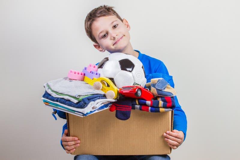 捐赠概念 孩子举行捐赠有衣裳、书和玩具的箱子 库存图片