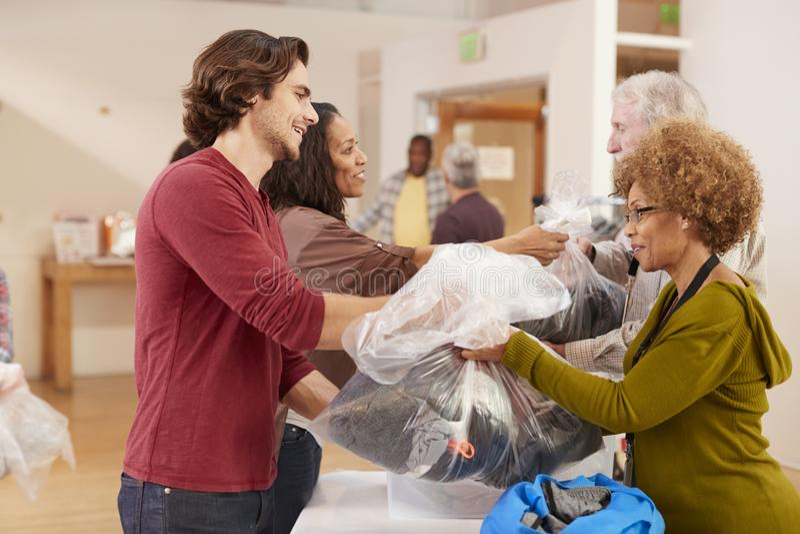 捐赠衣物的人们对慈善汇集在社区活动中心 库存照片