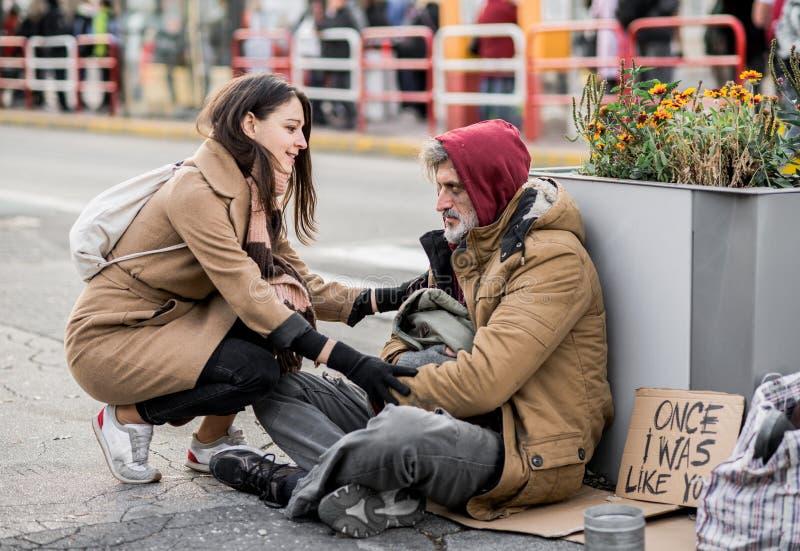 捐钱的年轻女人给坐在城市的无家可归的叫化子人 免版税库存照片