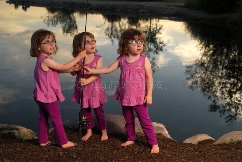 捕鱼三胞胎 免版税库存照片