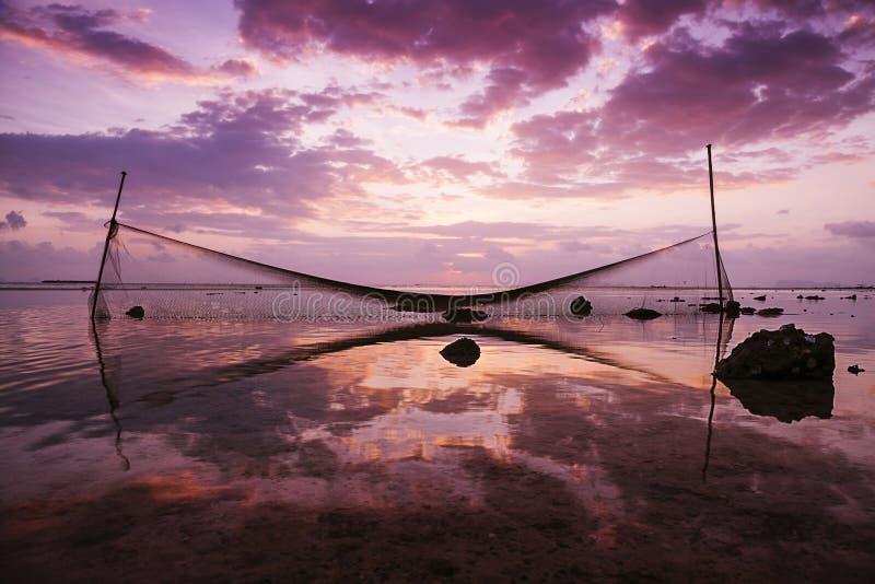捕鱼网在日落的水中被反射 免版税库存照片