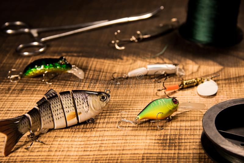 捕鱼装置、人为诱饵在掠食性动物在木背景,顶视图晃摇物和各种各样的诱饵绳子和钳子 免版税库存图片