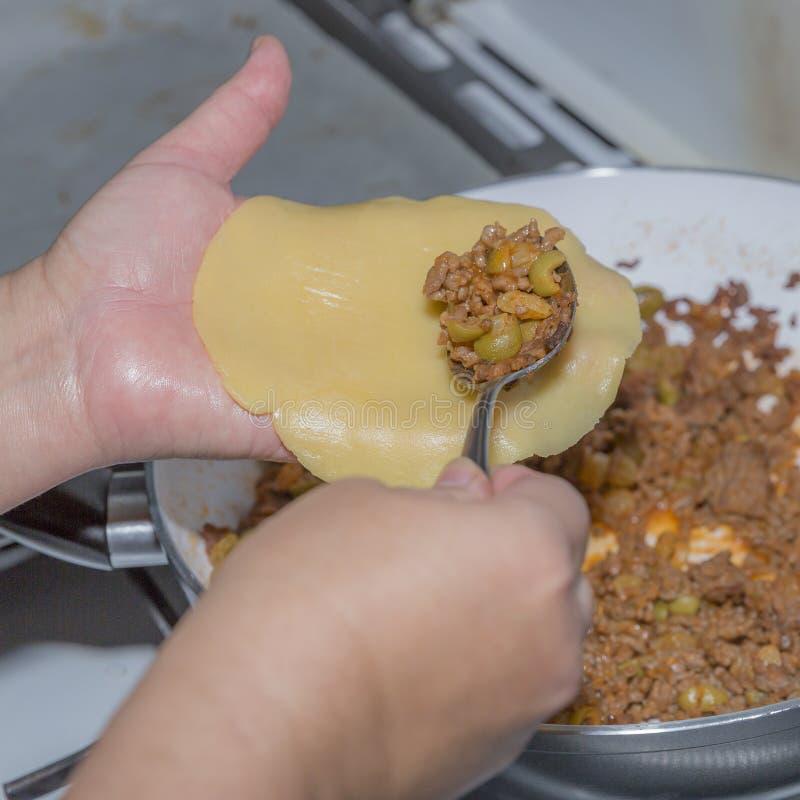 捞出绞细牛肉的女性手的图象准备用在empanada的新鲜的未加工的面团的上橄榄 库存图片
