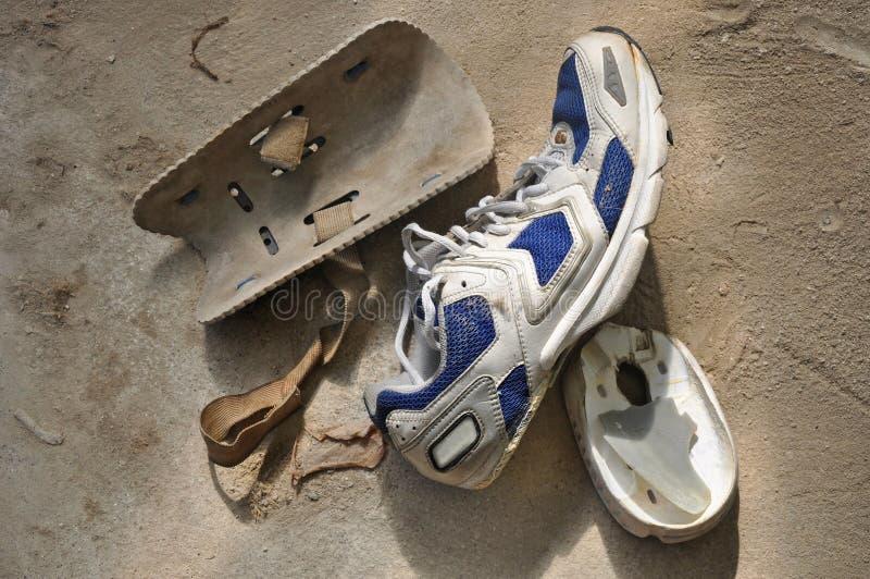 损坏的体育运动鞋子和老膝盖保护者 库存图片