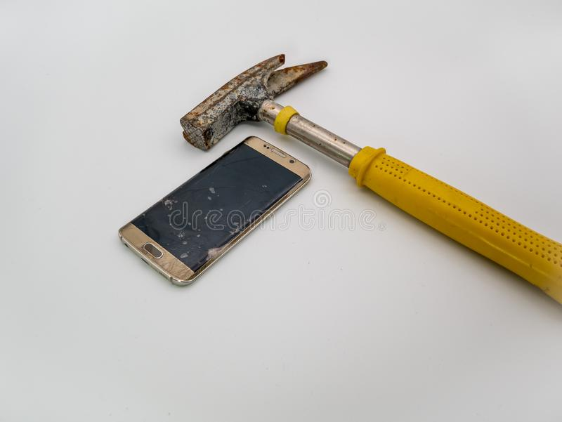 损坏的智能手机disply有锤子和白色背景的 库存图片