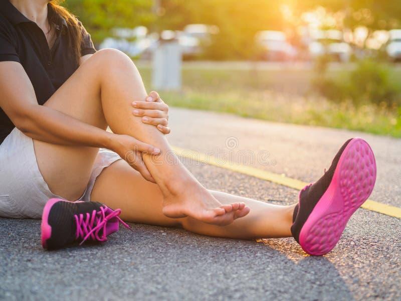 损害举行的连续伤害腿事故体育妇女赛跑者 免版税库存照片