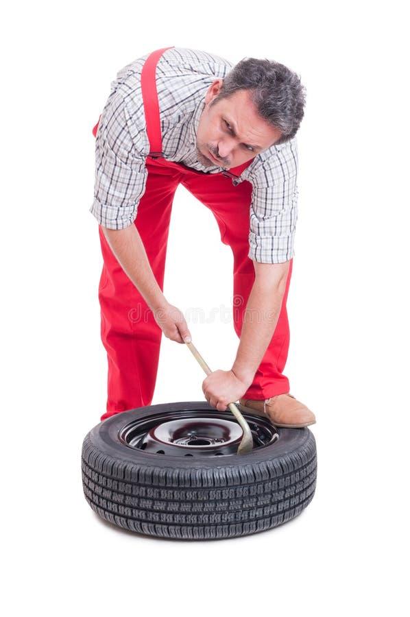 更换一个新的轮胎的疲乏的技工 免版税库存照片