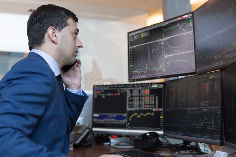 换在网上观看的图和数据分析在多个屏幕上的股票经纪人 库存照片