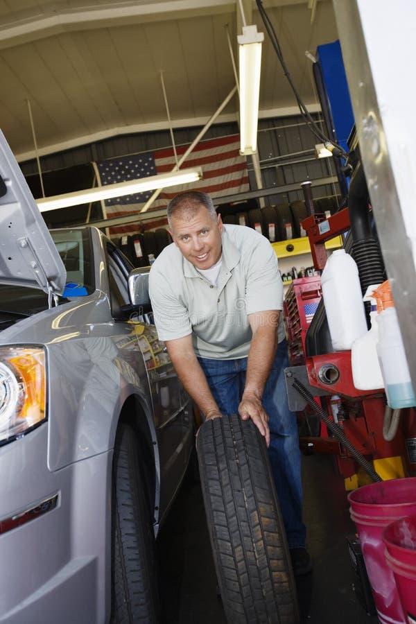 更换轮胎的汽车机械师 免版税库存照片