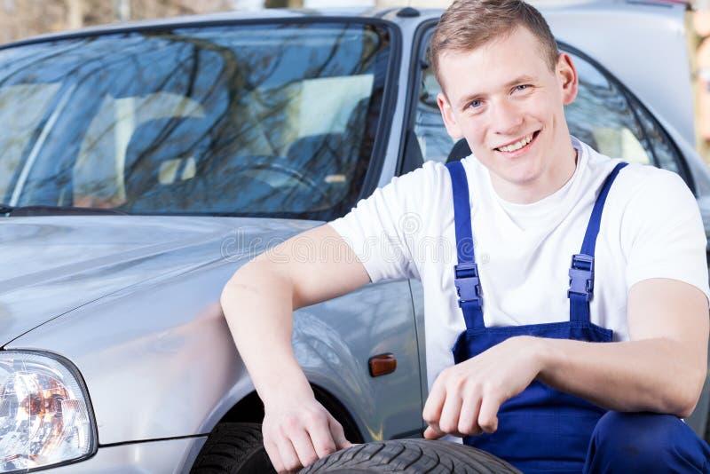 更换轮胎的高兴的技工 库存图片