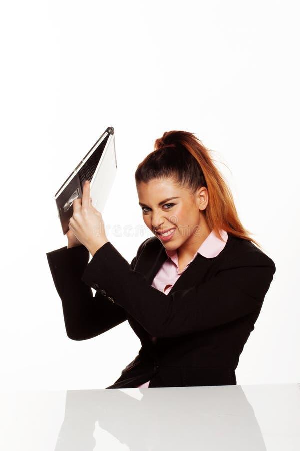 捣毁她的膝上型计算机的恼怒的女实业家 库存图片