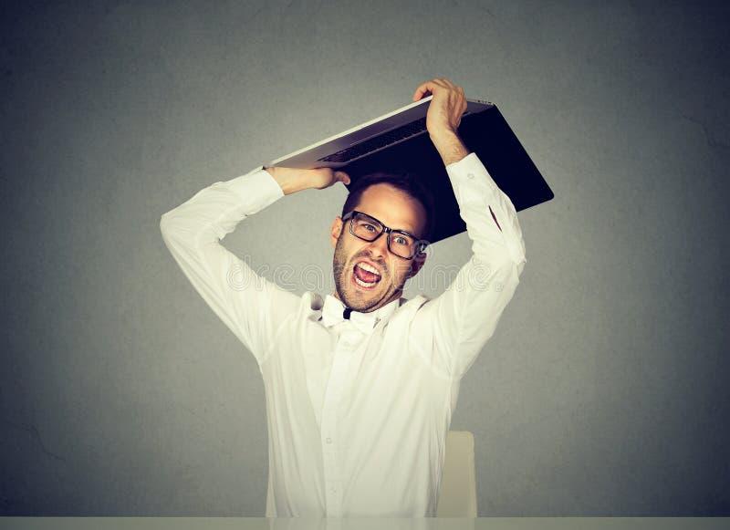 捣毁投掷的愤怒的商人他的便携式计算机 库存照片