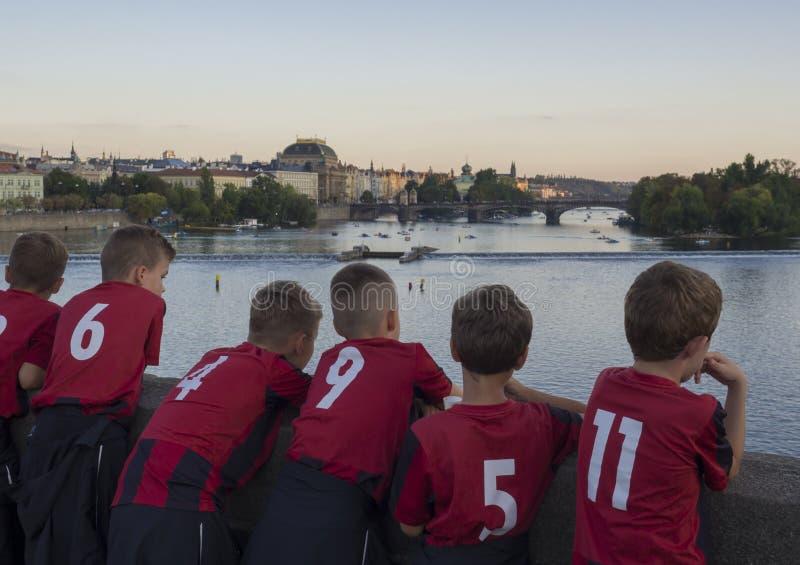 捷克,布拉格,2018年9月8日:小组看从布拉格老拖曳的查理大桥的红色橄榄球礼服的年轻男孩 免版税库存照片