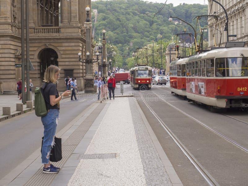 捷克,布拉格, 2018年5月9日:wating在国家戏院大厦的电车infront,电车轨道的人们到达  免版税库存图片
