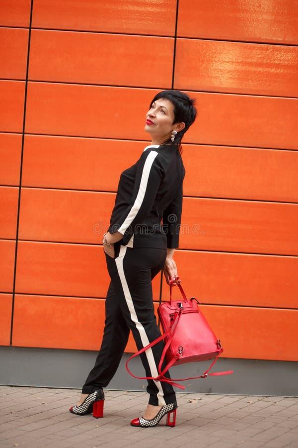 捷径深色的妇女室外画象时髦的衣服和红色袋子的,摆在橙色墙壁的时髦夏天成套装备 库存照片
