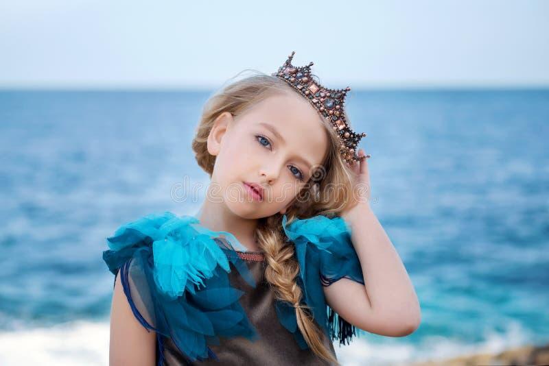掀动一个年轻公主女孩的画象冠和天蓝色礼服的她的头并且体贴看 免版税库存照片