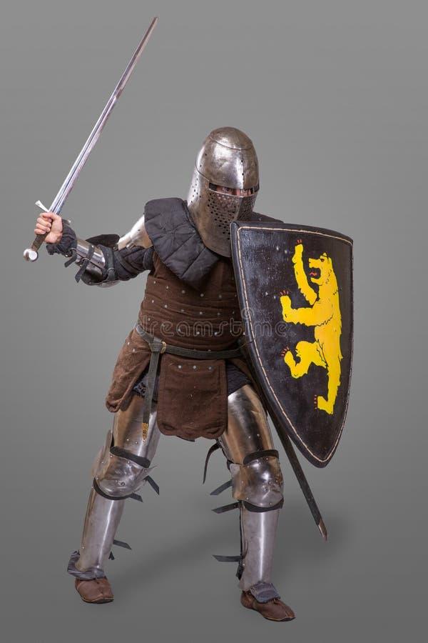 授以爵位在一件盔甲的呼吸与剑和盾在争斗关于灰色背景 免版税库存照片