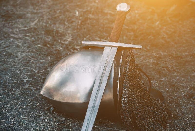 授以爵位` s盔甲,并且发光的金属说谎在地面上的,它投入了有皮革把柄的一把老钢剑 库存图片