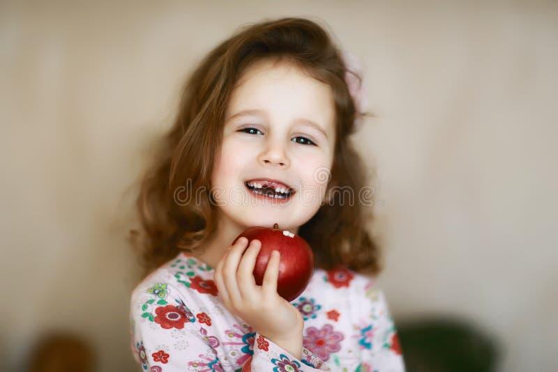 掉了乳齿一个愉快的孩子的画象,逗人喜爱的矮小的卷曲无牙的caroque女孩在她的手上微笑并且举行红色 库存图片