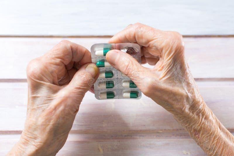 去掉药片的资深妇女手 库存图片