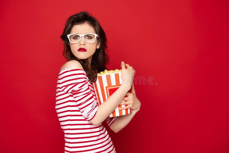 掌握箱子用玉米花的贪婪的深色的夫人 免版税库存图片