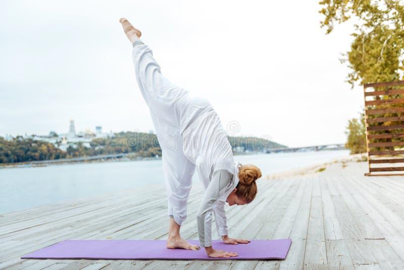 掌握asanas的女性瑜伽辅导员在水附近 库存照片