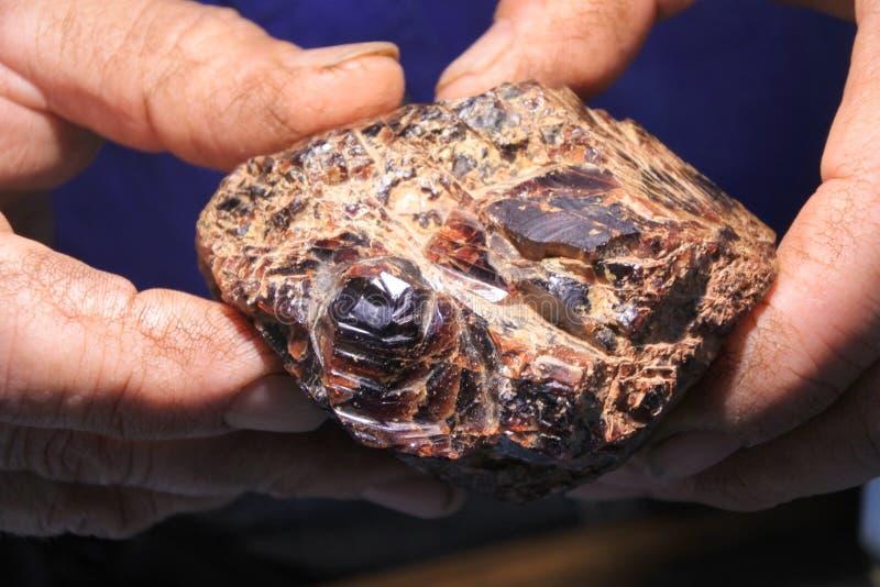 排序和重视未加工的石榴石宝石的人 库存照片