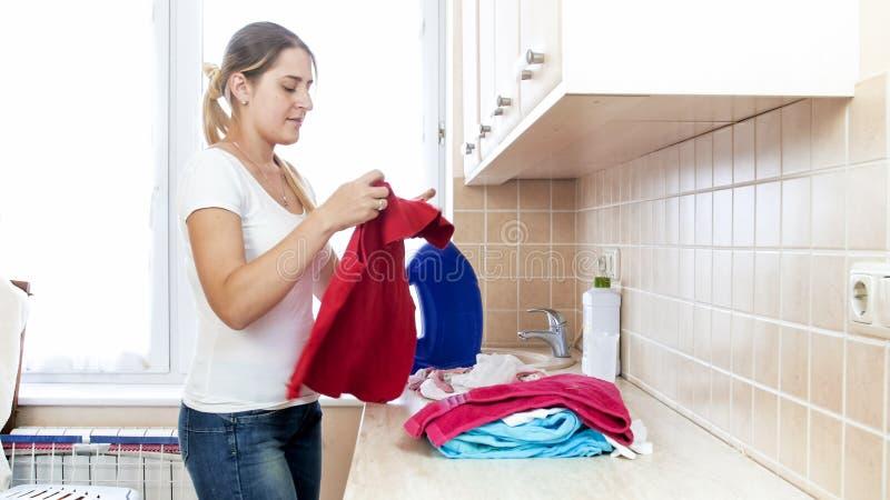 排序衣裳的年轻微笑的主妇在洗衣店以后 免版税库存照片