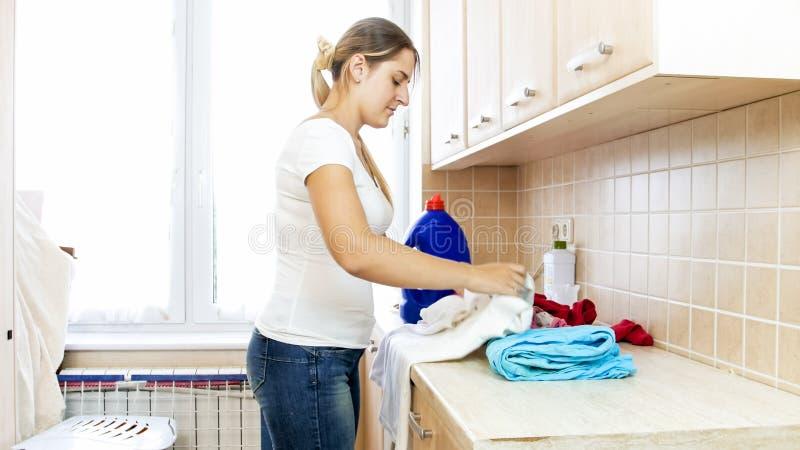 排序衣裳的美丽的少妇在洗衣房 免版税库存图片