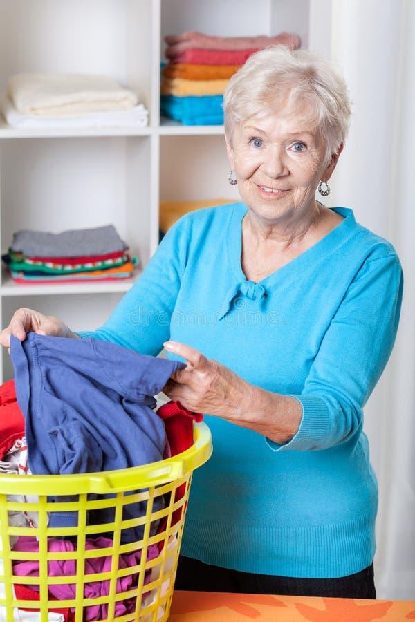 排序洗衣店的年长妇女 免版税库存图片