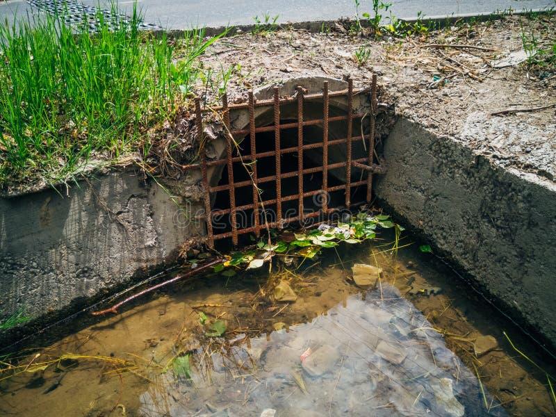 排水设备在路下的下水道排泄的污水或雨水 免版税库存图片