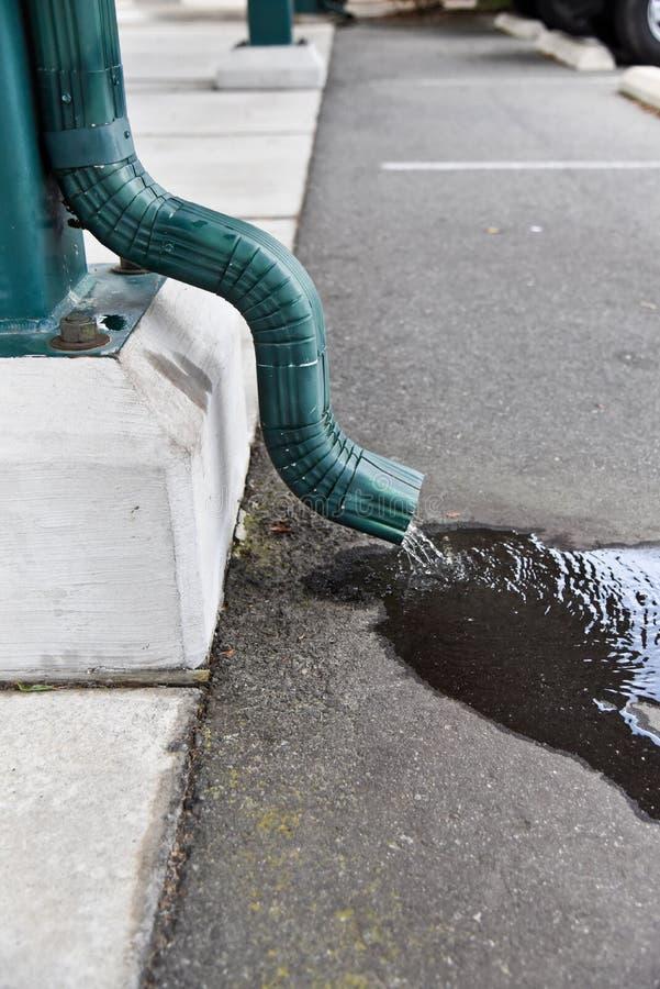 排泄暴雨水的绿色天沟对路面 免版税库存图片