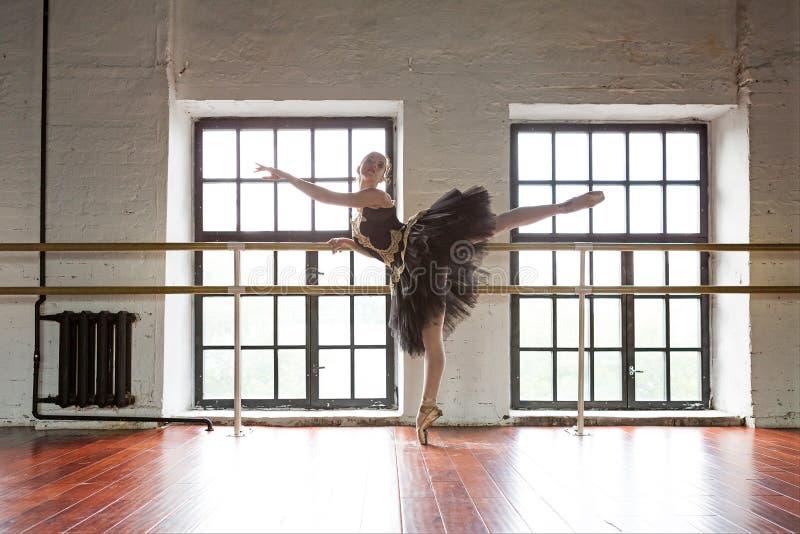 排练芭蕾舞女演员在大厅里 木地板,大窗口 美丽的芭蕾舞女演员在排练屋子 库存照片