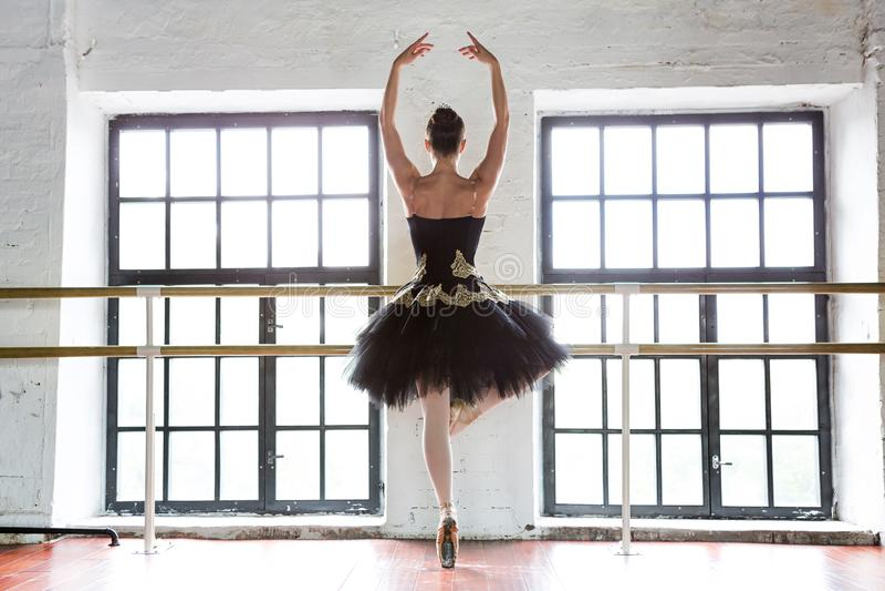 排练芭蕾舞女演员在大厅里 木地板,非常大窗口 美丽的芭蕾舞女演员在排练屋子 库存照片