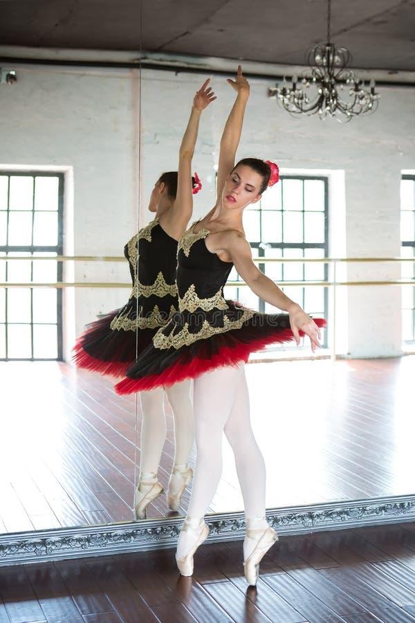 排练芭蕾舞女演员在大厅里 轻的绝尘室,木地板,大镜子 在镜子反映的芭蕾舞女演员 免版税库存照片