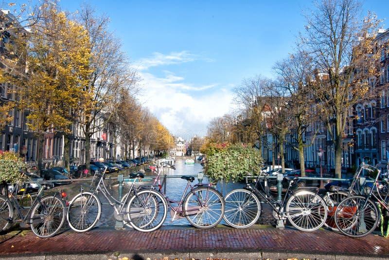 排行在阿姆斯特丹,荷兰运河的自行车一座桥梁  图库摄影