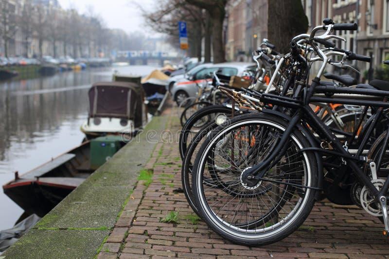 排行在阿姆斯特丹,荷兰运河的自行车一座桥梁  库存照片